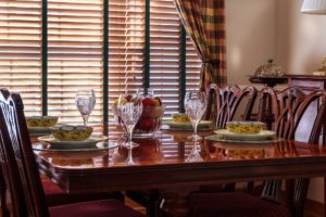Dining room with utensils, glasses and bowls and wooden blinds in the background
